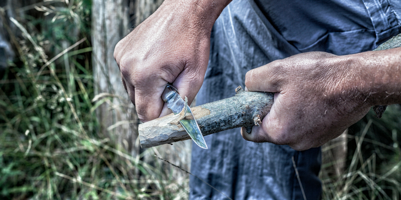 A man using his survival skills and knife to carve a piece of wood in order to build a shelter.