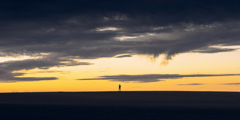 Horizon scanning during sunset, showing a silhouette of a man on the horizon.